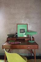 Grüne Tischleuchte und Bild auf dem Schreibtisch vor grauer Wand