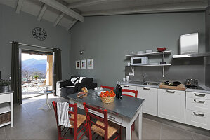 Table and chairs in kitchen with grey walls and access to terrace