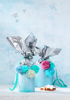 Handmade, festive gift containers made from tin cans decorate with pompoms