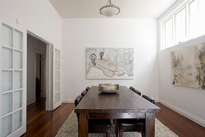 Rustic wooden table, leather chairs and modern artworks on wall in dining room