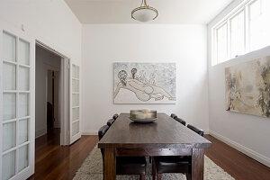 Rustikaler Holztisch mit Lederstühlen und moderne Kunstwerke an der Wand im Speisesaal