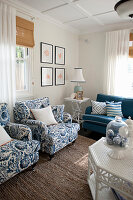 Armchairs, side table and sofa in living room with blue accents