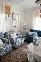 Polstersessel, Beistelltisch und Sofa im Wohnzimmer mit blauen Farbakzenten