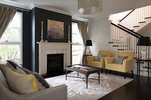 Pastellfarbene Polstersessel und Couchtisch im Wohnzimmer mit schwarz gestrichener Kaminwand, im Hintergrund Treppe