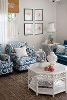 Weißer Rattantisch, blau-weiße Polstersessel und Beistelltisch im Wohnzimmer