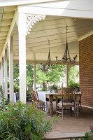 Holztisch mit Stühlen auf überdachter Terrasse mit Holzverzierung