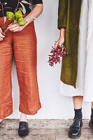 Zwei Frauen mit herbstlichen Zweigen in den Händen
