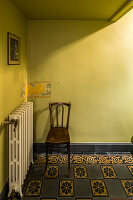 Chair against yellow wall with painted border on Art-Nouveau tiled floor