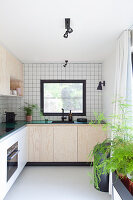Kitchen with white wall tiles and pale wooden cupboards