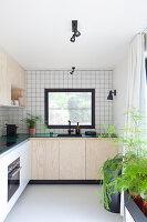 Küche mit weißen Wandfliesen und Schrankfronten aus hellem Holz