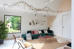 Dunkelgrünes Recamiere in Wohnzimmer mit Giebeldach und Holzelementen zur Wandgestaltung