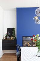 Schwarze Kommode in der Nische neben blauer Wand im Esszimmer