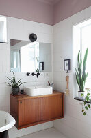 Countertop sink on mid-century cabinet in bathroom with dusky-pink ceiling