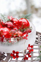 Red Christmas baubles in ice bowl with fairy lights