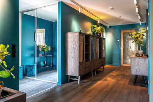 Hallway with dark wooden floor and turquoise walls