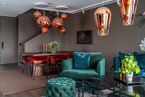 Turquoise velvet furniture in seating area with designer lamps