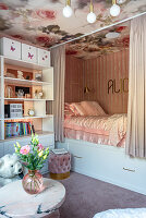 Girl's bedroom decorated in pink with cubby bed and bookcase