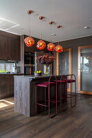 Elegant kitchen with dark wooden fronts and velvet bar stools at kitchen island