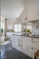 Large kitchen in Scandinavian country-house style with stone floor