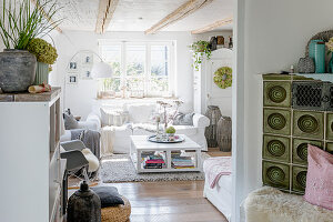 Green tiled stove and autumnal decorations in shabby-chic style in living room