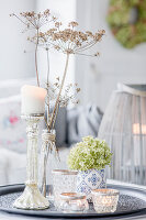 Autumnal arrangement of hydrangea and candle on table