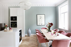 Dining table and chairs in open-plan kitchen with white cupboards and pale grey wall