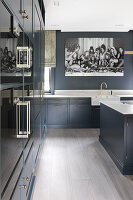Black-and-white photo in large, classic, blue-grey kitchen