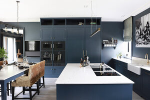 Island counter and dining table in large, classic, blue-grey kitchen