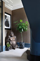 Gorilla statue and plants in pots with lion motif in hallway
