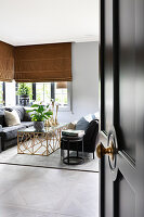 View through open panelled door with doorknob leading into elegant living room