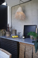 Raffia lampshade above worksurface of outdoor kitchen