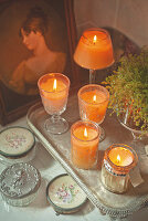 Arrangement of candles in vintage glass holders on silver tray
