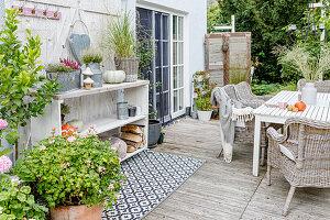 Terrasse im Herbst mit Gartenmöbeln, Outdoor-Teppich und Holzregal