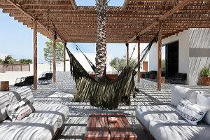 Hängematten und Loungebereich auf strohgedeckter Sonnenterrasse