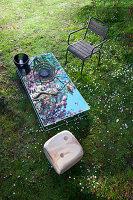 Spiegelglastisch, Armlehnstuhl und Zedernhocker in Würfelform auf Frühlingswiese