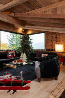 Red sledge, black sofa set and decorated Christmas tree in living room of chalet