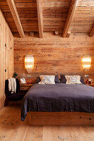 Double bed and elegant sconce lamps in bedroom in chalet