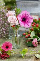 Blüten von Rose und Petunie in kleiner Flasche