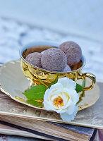 Goldene Kaffeetasse mit Pralinen und Rosenblüten