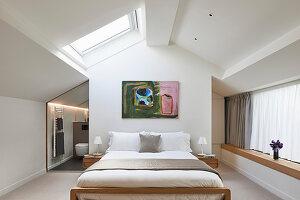 Doppelbett in hellem Schlafzimmer mit Dachfenster und Bad Ensuite