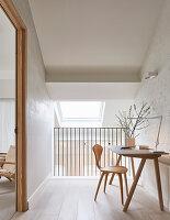 Schreibtisch mit Stuhl vor weiß getünchter Ziegelwand