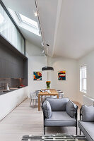 Sofa set, dining area and fitted kitchen in bright, open-plan interior