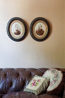 Scatter cushions on vintage leather couch below old photos on wall