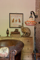 Scatter cushion on vintage leather armchair and standard lamp in front of stuffed hare on top of chest of drawers