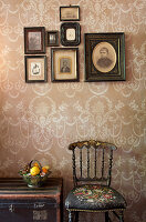Antique chairs and trunk below framed photos on patterned wallpaper