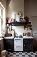 Gas cooker in kitchen counter and chequered floor in kitchen of period building