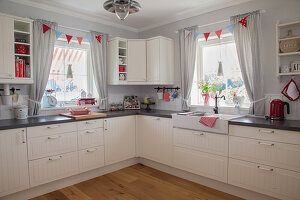 Modern, country-house-style kitchen with bunting in windows