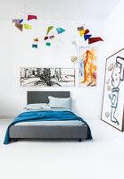 Graues Bett in Zimmerecke dekoriert mit modernen Wandbildern