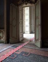 Moderne rot-weiß gemusterte Fliesen als Streifen ausgelegt auf antikem Mosaikboden