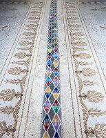 Moderne Fliesen mit bunten geometrischen Mustern ausgelegt auf antikem Mosaikboden